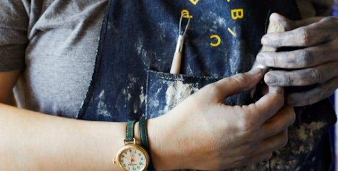 Artisan wearing an apron and a Shinola x Pewabic Runwell on their wrist